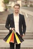 Het exclusieve winkelen De mensenklant draagt het winkelen zakken stedelijke achtergrond De succesvolle zakenman kiest slechts lu royalty-vrije stock foto's