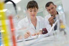 Het experimenteren met vloeistoffen in laboratorium stock afbeeldingen