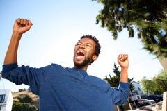 Het extatische knappe mens vieren met uitgestrekte wapens stock foto's