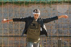 Het extravagante hipster mannelijke model luistert aan muziek in aard Het model draagt een leerjasje met klinknagel en een scarfE royalty-vrije stock foto