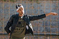 Het extravagante hipster mannelijke model luistert aan muziek in aard Het model draagt een leerjasje met klinknagel en een scarfE stock afbeelding