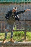 Het extravagante hipster mannelijke model luistert aan muziek in aard Het model draagt een leerjasje met klinknagel en een scarfE stock foto's