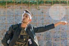 Het extravagante hipster mannelijke model luistert aan muziek in aard Het model draagt een leerjasje met klinknagel en een scarfE royalty-vrije stock afbeeldingen