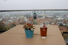 Het F-glas bier op houten lijst aangaande de koffie in het kasteel van Bratislava stock foto's