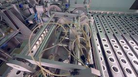 Het fabrieksmechanisme verplaatst wafeltjekoppen met roomijs van een rechte transportband aan dalende  stock videobeelden