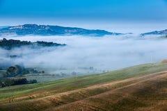 Het fairytale mistige landschap van Toscaanse gebieden bij zonsopgang stock foto