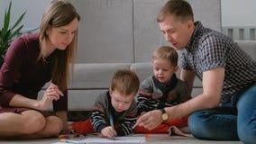 Het familiemamma, de papa en twee tweelingbroers trekken zich tellers en gevoelde pennen zittend op de vloer samen royalty-vrije stock afbeeldingen