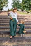 Het familiemamma met dochter in uitstekend retro linnen kleedt zich met boeket van bloemen lopend dageraad treden in een parktuin Royalty-vrije Stock Afbeelding