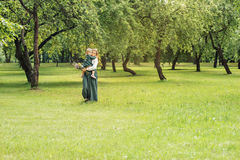 Het familiemamma met dochter in uitstekend retro linnen kleedt zich met boeket van bloemen lopend in een bos van de parktuin Stock Fotografie