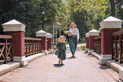 Het familiemamma met dochter in uitstekend retro linnen kleedt zich met boeket van bloemen lopend in een parktuin Royalty-vrije Stock Afbeeldingen