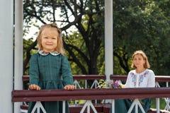 Het familiemamma met dochter in uitstekend retro linnen kleedt zich met boeket van bloemen zittend in het tuinhuis Stock Foto