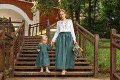 Het familiemamma met dochter in uitstekend retro stijllinnen kleedt zich met boeket het lopen dageraad houten treden in een parkt Stock Foto
