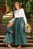 Het familiemamma met dochter in uitstekend retro stijllinnen kleedt zich met boeket het lopen dageraad houten treden in een parkt Stock Fotografie