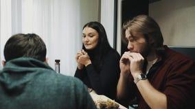 Het familiepaar eet sushi en dranken terwijl het spreken aan vriend bij dinerlijst stock videobeelden