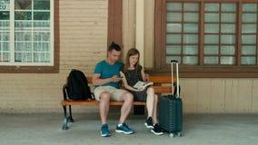 Het familiepaar wacht op trein met telefoon en boek Technologie versus traditie stock video