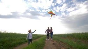 Het familieweekend, de jonge moeder en de vader met zoon genieten van gang met vliegende vlieger tijdens weekend in platteland op stock videobeelden
