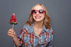 Het fantastische meisje houdt een rode lolly in haar handen Zij weard donkere glazen met rode rand Zij glimlacht geïsoleerde stock foto's