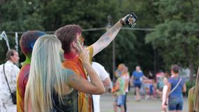 Het festival van Holikleuren, groepsmensen in helder poeder doet selfi op androïde op openlucht, maakt de jeugd met kleurenhaar stock videobeelden