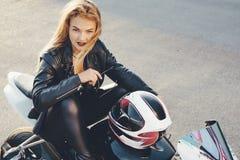 Het fietsermeisje in een leer kleedt zich op een motorfiets stock afbeelding