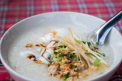 Het fijngehakte ei van de rijsthavermoutpap varkensvlees in kom met de achtergrond van het geruit Schots wollen stofpatroon stock afbeeldingen