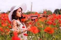 Het Filipijnse model speelt de viool sorounded door rode papavers Stock Afbeelding