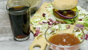 Het filteren omhoog op snel die voedseldiner van hamburger met gebraden gerechten op houten lijst wordt gemaakt stock footage