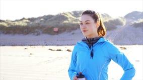 Het filteren van schot van geschikt vrouwen drinkwater op strand stock video