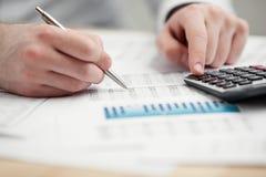 Het financiële gegevens analyseren. Het tellen op calculator. Stock Afbeelding