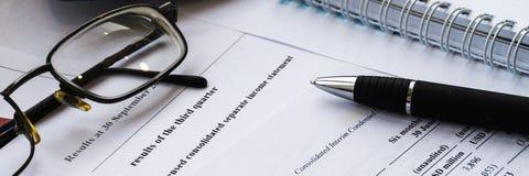 Het financiële verslag van de inkomensverklaring met pen Financiële analyse - businessplan royalty-vrije stock foto