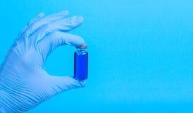 Het flesje met een vaccin of een behandeling voor het houden van een blauw gloves Royalty-vrije Stock Afbeelding