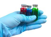 Het flesje met een vaccin of een behandeling voor het houden van een blauw gloves Stock Fotografie