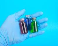 Het flesje met een vaccin of een behandeling voor het houden van een blauw gloves Royalty-vrije Stock Foto's