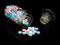 Het flesje van het glas met een glaskurk en groepeert een pil. Stock Foto