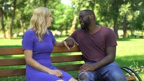 Het flirten paarzitting op bank in park en samen het spreken, het besteden tijd stock video