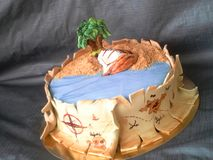 Het fondantje van de piraatcake met schip, palm, zand en kaart van gouden rijkdom stock foto's