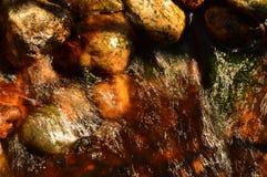 Het fonkelen zonlicht in de stroom van zuiver bronwater door de steenbarrière stock fotografie