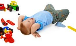 Het fooling van het kind op de vloer onder het speelgoed Stock Fotografie