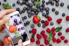 Het fotograferen van voedsel Handen die beeld van organische verse geoogste bessen met smartphone nemen Royalty-vrije Stock Foto's