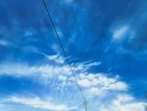 Het fotografische beeld van een machtspool met draden tegen een blauwe hemel met cirrus betrekt royalty-vrije stock afbeelding