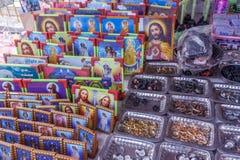 Het fotokader van moeder Mary, Jesus, en platen van verschillende met maat ringen blokkeerde in een straatwinkel voor verkoop, Ch stock afbeelding