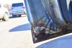 Het fragment van een auto met roest het element van het autolichaam is aangetast Concept: corrosieweerstand, de reparatie van het royalty-vrije stock foto