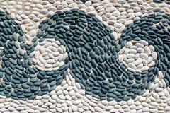 Het fragment van a pebbled bestrating met een patroon van golven stock foto's
