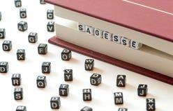 Het Franse woord die sagesse die wijsheid betekenen met brieven wordt geschreven tussen een boek worden opgesloten dient en sprei stock afbeelding