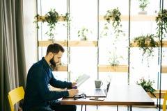 Het freelance mens werken online met laptop en het houden van documenten in een modern bureau stock foto