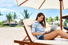 Het freelance werk Bedrijfsvrouw die Computer op Strand met behulp van Het online werk stock foto's