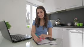 Het freelance werk, gelukkige jonge vrouw die aan laptop computer werken terwijl het koken in keuken stock video