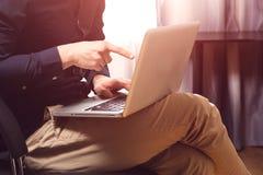 Het freelance werk Toevallige geklede mensenzitting als voorzitter binnen zijn het vlakke werken aan computer die met vinger rich Stock Afbeeldingen