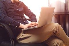 Het freelance werk Zitting van de close-up de toevallige geklede mens als voorzitter binnen zijn het vlakke werken aan computer d Stock Foto