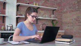 Het Freelancermeisje dat in oogglazen op laptop toetsenbord typt en schrijft nota's in klembord tijdens online het werk zitting b stock footage