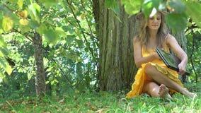Het Freelancerwijfje in kleding zit dichtbij boomboomstam en laptop van het begingebruik computer in zonnig park 4K stock footage